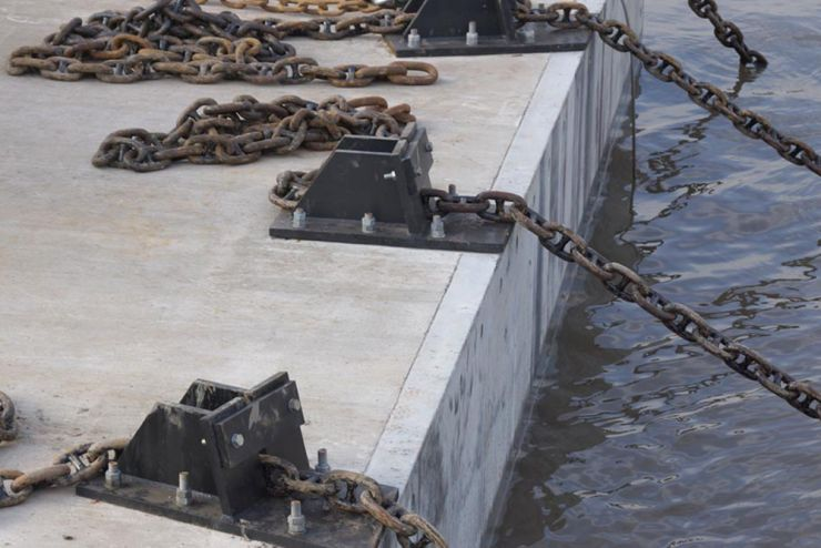 Mutliple lengths of chain attached to mooring points on concrete with piles of chain behind them